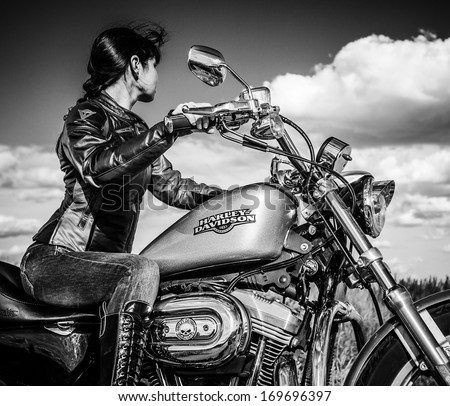 MOSCOW, RUSSIA-JULY 7, 2013: Biker girl on Legendary bike Harley Sportster. Processed in B&W. Harley-Davidson sustains a large brand community which keeps active through clubs, events, and a museum. - stock photo