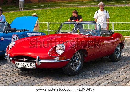"MOSCOW,RUSSIA-JULY 10: Red Jaguar E-Type year 1963 is on display at the start annual Rally of classical cars ""Zolotoe kol'co"" on Red Square with more than 30 crews, on July 10, 2010 in Moscow, Russia - stock photo"