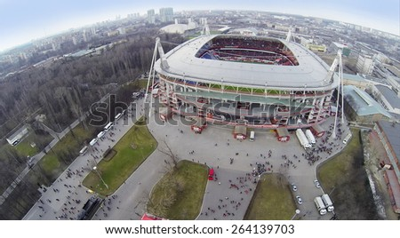 MOSCOW, RUSSIA - MAR 30, 2014: Cityscape with people on tribunes of Locomotive sports stadium at spring day. Aerial view - stock photo