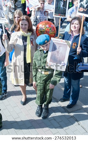MOSCOW, RUSSIA - MAY 09, 2014: A boy wearing soldier's uniform holds portrait of his grandfather who fought in WWII.  March of 'Immortal Regiment' - stock photo