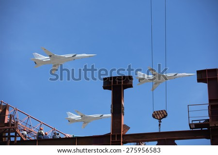 MOSCOW, RUSSIA - MAY 7, 2015: Builders are looking at aircraft from the roof of the building. Rehearsal of parade devoted to May 9, 70-th Victory Day in World War II. May 7, 2015 in Moscow.  - stock photo