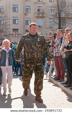 MOSCOW/RUSSIA - MAY 9: Special squad officer in uniform decorated with numerous orders and medals and his dougter walk arm in arm during festivities devoted to Victory Day on May 9, 2013 in Moscow.  - stock photo