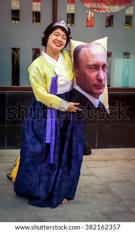 MOSCOW, RUSSIA - MAY 9: Unidentified woman in Chinese folk costume holding a pillow with a portrait of winking Vladimir Putin in Moscow, Russia on May 9, 2015. - stock photo