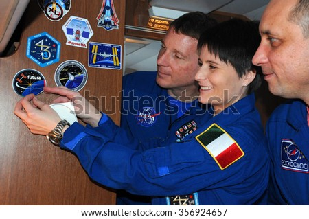 MOSCOW, RUSSIA - NOVEMBER 11, 2014: ISS Expedition 42/43 crewmembers T.Virts (left), S.Cristoforetti (center) and A.Shkaplerov (right) affix a decal aboard aircraft on the way to Baikonur cosmodrome - stock photo