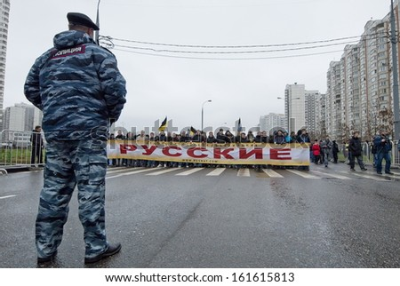 """MOSCOW, RUSSIA - NOVEMBER 4: Unidentified policeman stands opposite the crowd of Russian nationalists during annual """"Russian March"""" in Moscow, Russia on November 4, 2013. Caption means """"Russians"""". - stock photo"""