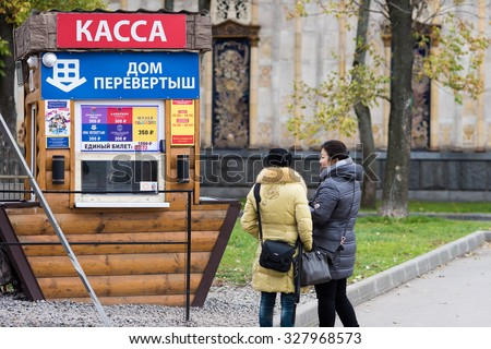 Moscow, Russia - October 12, 2015: Exhibition of achievements of national economy (VDKhH). Women near ticket service of attraction in the form of an inverted house. - stock photo