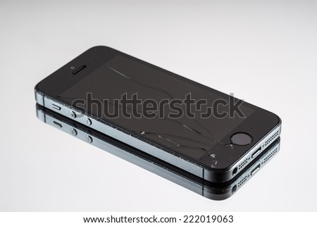MOSCOW, RUSSIA - OCTOBER 6, 2014: Photo of a broken iPhone 5. iPhone 5 is a smartphone developed by Apple Inc. It is part of the iPhone line. iPhone is world favorite smartphone. - stock photo