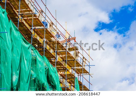 MOSCOW, RUSSIA - SEPTEMBER 08, 2012: Workers assemble scaffolds of the tall building under renovation against the background of blue sky and white clouds. Renovation of Arbat street - stock photo