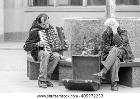 MOSCOW, RUSSIAN FEDERATION - APRIL 14: Street musician playing accordion on bench in the city, on April 14, 2016 in Novokuznetskaya street, Moscow, Russia . - stock photo