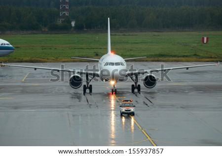 MOSCOW - SEPTEMBER 6: Yamal Aero passenger plane in Domodedovo International, Moscow on September 6, 2013. Yamal Aero passenger plane with enabled taxi and navigation lights follows the escort car. - stock photo