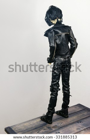Most jointed doll a man dressed in black leather pants and a jacket is standing on a wooden bridge before the precipice and looking down - stock photo