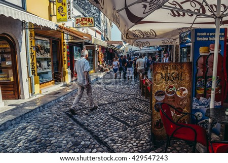 Mostar, Bosnia and Herzegovina - August 25, 2015. People walk at famous paved Mala Tepa Street with many tourist shops and restaurants in Mostar  - stock photo