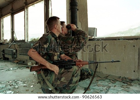 MOSTAR, BOSNIA - AUGUST 16: A Bosnian-Croat HVO sniper team peers out of a destroyed bank building at Bosnian-Muslim civilians on the east side of this divided city in Mostar, Bosnia on Aug 16, 1993. - stock photo