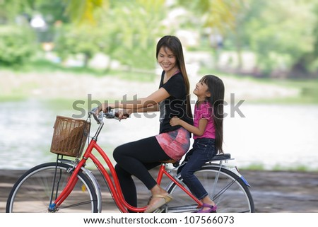 Mother and a daughter cycling bicycle at the park - stock photo
