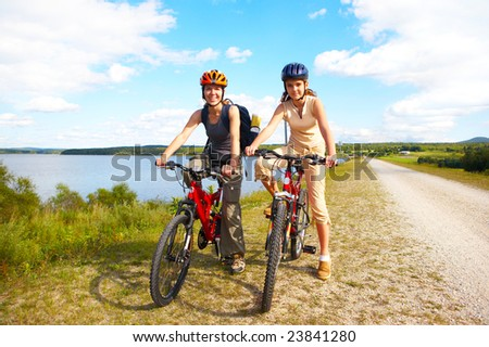 Mother and a daughter cycling near the lake - stock photo