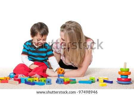 Mother and a little son are playing on the carpet with blocks; isolated on the white background - stock photo
