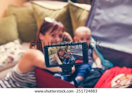 Mother And Adorable Baby Boy In Suitcase Taking Selfie While They Are Getting Ready For Traveling - stock photo