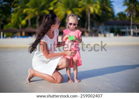 Mother and adorable girl during beach vacation - stock photo