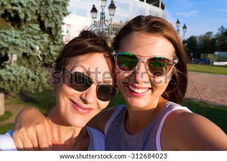 Mother and adult daughter are doing selfie in park in summer going crazy and laughing. Sunset light.Happy and positive emotions.Two friends on vacation.Parents and teenagers.Summer self-portrait - stock photo