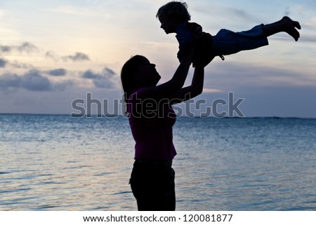 mother and baby at sunset beach - stock photo