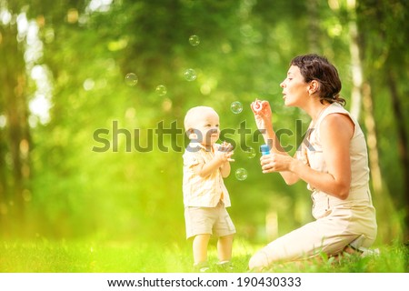 Mother and baby blowing bubbles in the park. - stock photo