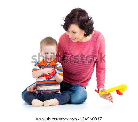 Mother and baby boy having fun with musical toys. Isolated on white background - stock photo