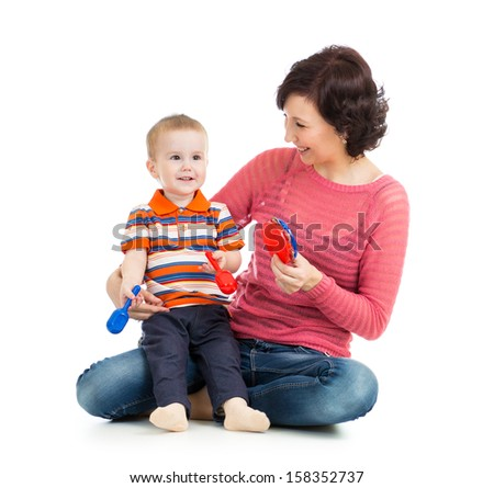 Mother and baby boy play with musical toys - stock photo