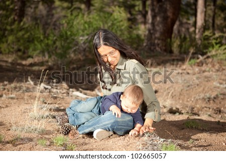 Mother and baby boy studying things in nature - stock photo