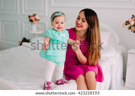 Mother and baby closeup portrait,  european family  adorable small girl, mom and kid having fun indoor, parents joy, holding little child, healthy toddler and mommy, happiness concept - stock photo