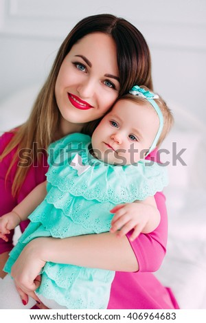 Mother and baby closeup portrait, happy faces, european family picture, adorable small girl, mom and kid having fun indoor, parents joy, holding little child, healthy toddler and mommy - stock photo