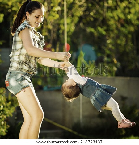 Mother and baby daughter are playing outdoors. Young mom and her cute little baby-girl are having fun in the sunny garden. Happy childhood and motherhood concept. Instagram style. - stock photo