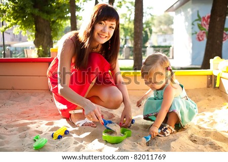 Mother and baby daughter playing in the sandbox - stock photo