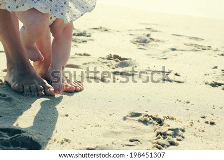 mother and baby feet at the beach sand - stock photo