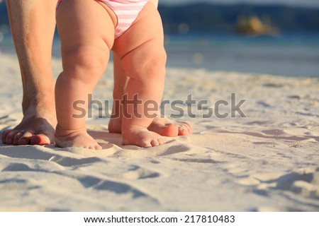 Mother and baby feet walking on sand beach - stock photo