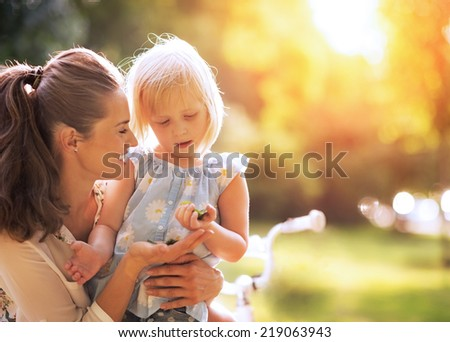 Mother and baby girl having fun outdoors - stock photo