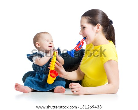 Mother and baby girl having fun with musical toys. Isolated on white background - stock photo