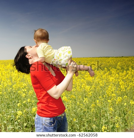 Mother and baby girl in a rapeseed field - stock photo