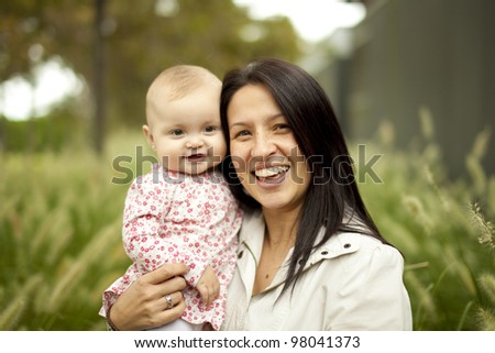 Mother and Baby Girl in front of tall grass at the Park - stock photo