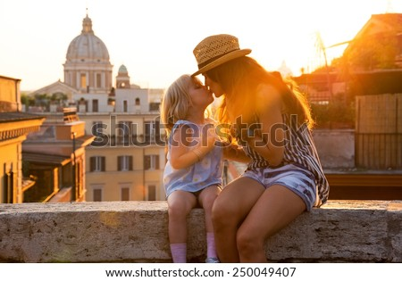 Mother and baby girl kissing while sitting on street overlooking rooftops of rome on sunset - stock photo