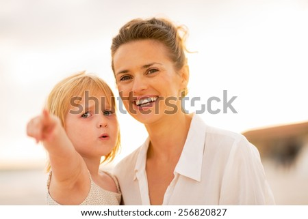 Mother and baby girl pointing while on beach at the evening - stock photo