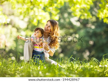 Mother and baby girl sitting and relaxing in park. - stock photo