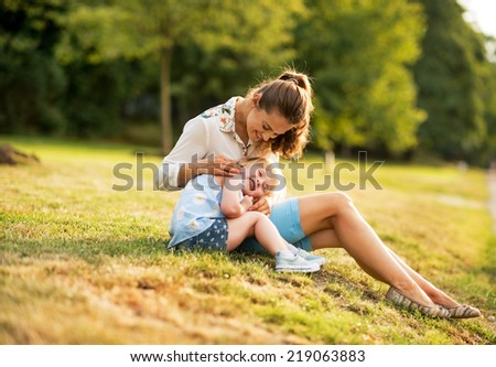 Mother and baby girl sitting outdoors in the evening - stock photo