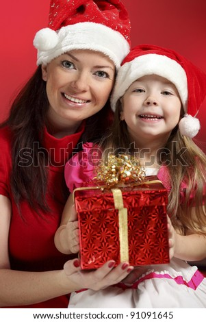 Mother and  baby girl with christmas gift - stock photo