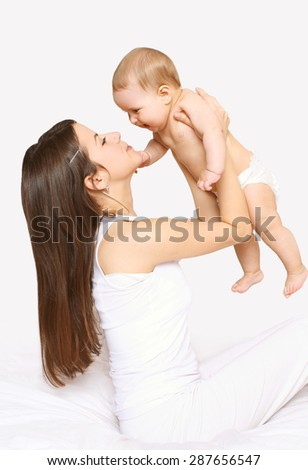 Mother and baby having fun together, mom playing with infant on the bed - stock photo