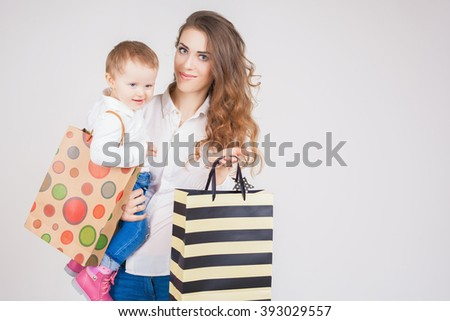 Mother and baby holding bags with purchases and toys. Shopping with child. They walking and looking at camera. Fashion baby clothes. Jeans. Boots, shoes. Today's children and mothers - stock photo