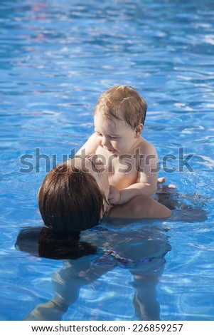 mother and baby in swimming pool embraced looking themselves - stock photo