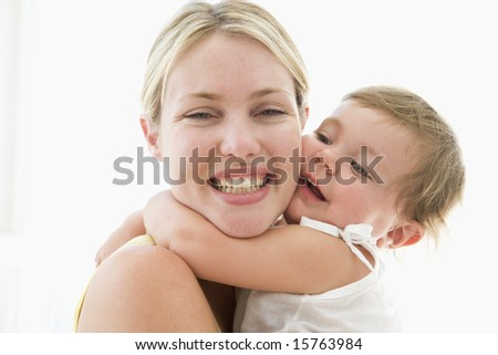 Mother and baby indoors hugging and smiling - stock photo