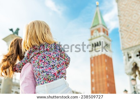 Mother and baby looking on campanile di san marco in venice, italy - stock photo