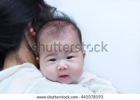 Mother and baby. Lovely girl resting on her mother's shoulder. Asian baby looking at camera. - stock photo