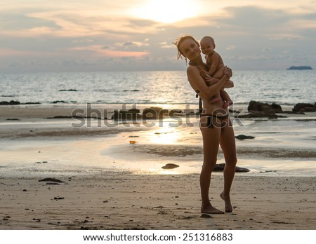 Mother and baby on the sunset - stock photo